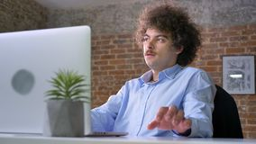 Idea coming to mind of nerd programmer with volume curly hair, working on laptop and sitting in modern office.  stock footage