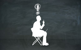 Idea concept. Abstract sitting man silhouette with lamp over head in chalkboard room. Idea  concept. 3D Rendering Stock Images