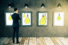 Idea concept. Back view of thoughtful businessman looking at wall with creative light bulb images in room with wooden floor and ceiling lamps. Idea concept. 3D Stock Images