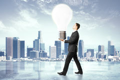 Idea concept, businessman carries a light bulb Royalty Free Stock Photo