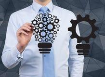 Idea concept. Businessman drawing gears in form bulb, idea concept Stock Photo