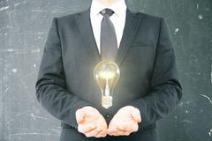 Idea concept businessman holding bulb Royalty Free Stock Images