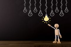 Idea concept, choosing the best idea, Brainstorming, Innovative Wooden Stick Figure pointing at a yellow light bulb. Copy space royalty free stock photography