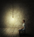 Idea concept. Creative idea concept with a man sitting in a dark room, looking at a lightbulb Royalty Free Stock Images