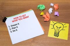 Idea concept with crumpled paper lightbulb and colored spiral notepad with pen on wooden desktop. How to get what you want. Idea concept with crumpled paper royalty free stock photos