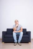 Idea concept - dreaming man sittin on sofa over white wall Royalty Free Stock Photos