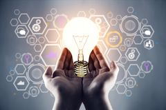 Idea concept. Female hands holding glowing lamp on abstract blurry background with business hologram. Idea concept Stock Photography