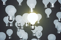 Idea concept with glowing light bulb on a black background Royalty Free Stock Images