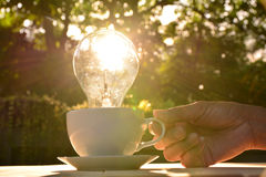 idea concept with light bulbs in coffee cup and hand of human ho Stock Image