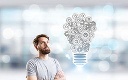 Idea concept metallic gear bulb. Idea concept with bearded man looking at abstract lightbulb made of metallic gears on blurry background Stock Image