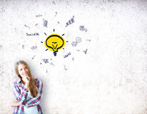 Idea concept. Portrait of thoughtful young lady on concrete background with creative lamp sketch. Idea concept Royalty Free Stock Image