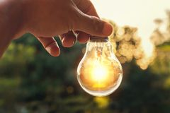 Idea concept of power energy with hand holding light bulb and su. Nset in nature Stock Photography