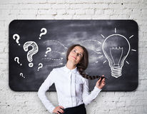 Idea concept. Pretty thoughtful girl on brick background with question marks and light bulb sketch on chalkboard. Idea concept Royalty Free Stock Image