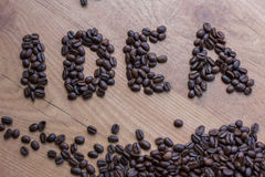 Idea concept sign drawn among brown roasted beans  of coffee. Idea concept sign drawn among brown well roasted coffee beans Royalty Free Stock Images