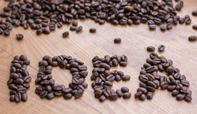 Idea concept sign drawn by brown roasted coffee beans. Idea concept sign drawn among brown well roasted coffee beans Stock Image