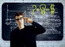 Idea concept. Thoughful businessman with head put to temple as a gun standing in front of chalkboard with mathematical formulas. Idea concept Stock Photo
