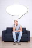 Idea concept - thoughtful man sitting on sofa at home. And blank bubble Royalty Free Stock Images