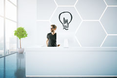 Idea concept. Thoughtful young businessman at reception desk with drawn light bulb. Idea concept. 3D Rendering Stock Photography