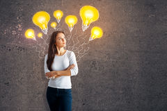 Idea concept. Thoughtful young european woman on concrete background with drawn yellow lamps. Idea concept stock image