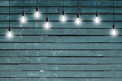 Idea concept - Vintage incandescent bulbs on blue wooden wall Stock Image