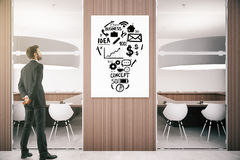 Idea concept. Young businessman in modern wooden interior looking at whiteboard with business sketch. Idea concept. 3D Rendering Stock Image