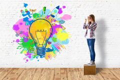 Idea concept. Young girl standing in room with business sketch and lamp. Idea concept Stock Photos
