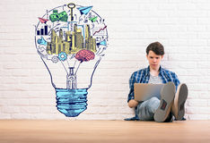 Idea concept. Young man sitting on wooden floor and using laptop on white brick wall background with creative colorful business sketch inside light bulb. Idea Stock Images