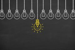 Idea concepts with light bulbs on a chalkboard background. Working Stock Images