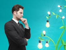 Idea and contemplate concept. Young european businessman with abstract light bulb tree. Idea and contemplate concept. 3D Rendering stock illustration