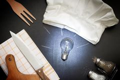 Idea for cooking food abstract concept with bulb and chef`s hat in the kitchen royalty free stock photo
