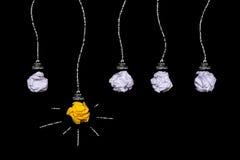 Idea creativa del papel arrugado Una bombilla ardiente en un fondo negro Imagen de archivo libre de regalías
