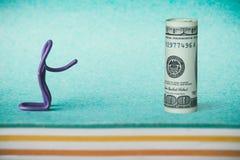 Idea creativa, el concepto de dinero que adora, un clip bajo la forma de hombre que arquea a un billete de dólar Imágenes de archivo libres de regalías