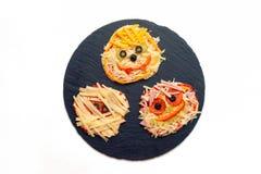Idea de la comida de Halloween - pizza hecha en casa, mini pizzas adornadas con las arañas y momias para Halloween Imagenes de archivo