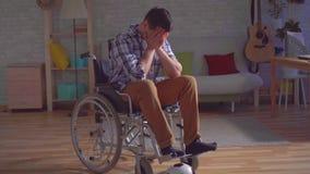 Idea del concepto de terminar una carrera de los deportes, hombre discapacitado triste en una silla de ruedas adentro con una bol almacen de metraje de vídeo