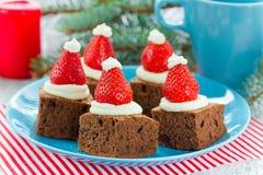 Idea del postre de los brownie del sombrero de Papá Noel de la Navidad, brownie de la torta con cr Fotografía de archivo