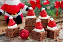 Idea del postre de los brownie del sombrero de Papá Noel de la Navidad, brownie de la torta con cr Foto de archivo