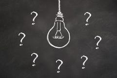 Idea della lampadina del gesso con i punti interrogativi su una lavagna royalty illustrazione gratis