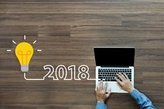 Idea della lampadina 2018 nuovi anni con lavorare al computer portatile Fotografia Stock