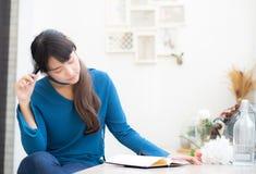 Idea di pensiero sorridente del bello del ritratto giovane scrittore asiatico della donna e scrivere sul taccuino o sul diario co immagini stock libere da diritti