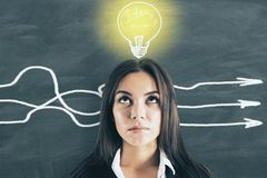 Idea and different direction concept. Portrait of attractive young european businesswoman with arrows and lamp sketch on chalkboard background. Idea and stock image
