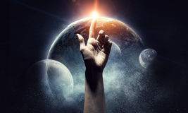 Idea of Earth creation. Human hand pointing with finger as symbol of creation. Elements of this image are furnished by NASA Stock Photo