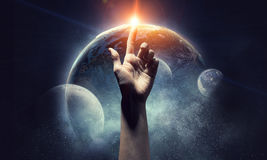 Idea of Earth creation    . Mixed media. Human hand pointing with finger as symbol of creation. Elements of this image are furnished by NASA Royalty Free Stock Image