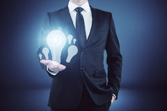 Idea and enlightenment concept. Businessman holding glowing lamps in abstract gradient interior. Idea and enlightenment concept royalty free stock photo
