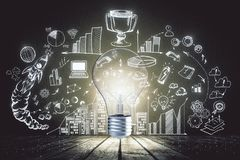 Idea and finance concept. Creative glowing lamp with business sketch. Idea and finance concept Royalty Free Stock Photography