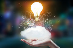 Idea and finance concept. Hand holding abstract cloud with business hologram and glowing light bulb on blurry background. Idea and finance concept. 3D Rendering Stock Image