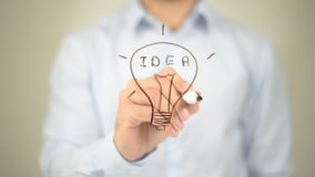 Idea, Glowing Bulb Concept,  Man writing on transparent screen Royalty Free Stock Photos