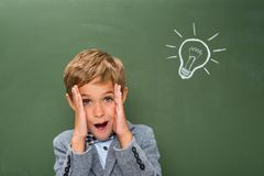 Idea. Happy schoolboy next to chalkboard with lightbulb sign Stock Photos