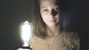 The idea has come true! The light bulb in the hand of a beautiful young girl is lit. stock video