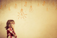 Idea. Hipster kid thinking. Idea concept. Drawing bulb lump. Retro toned Royalty Free Stock Photography