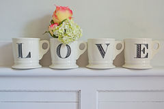 Idea for Home Decoration for Love. And Affection. White backgound with four white mugs each with the letter L, O, V and E written on it. In one of the mugs Stock Photography